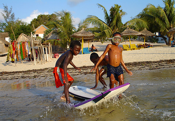 Barn som leker i strandkanten i Madagaskar.