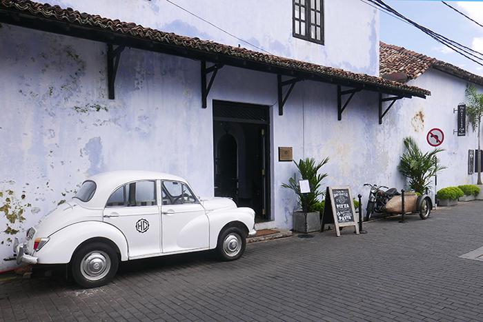 Bildetekst: Gatebilde med en hvit boble og pastellblå husfasade.