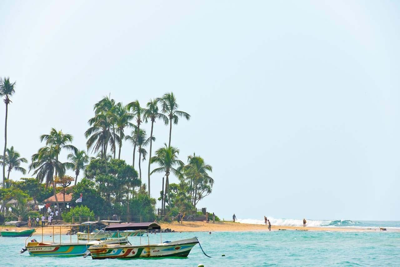 Bildetekst: Bilde av en sandstrand med bølger og palmer, fargerike småbåter i forgrunnen.
