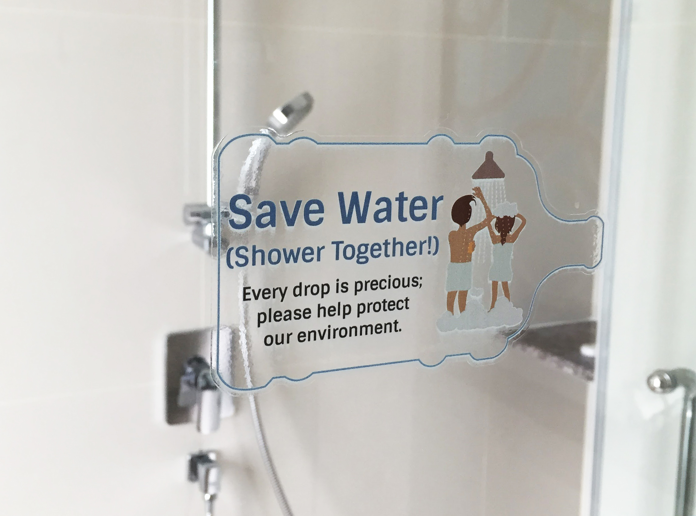 Hotelldusj med skriften Save Water Shower Together på døren