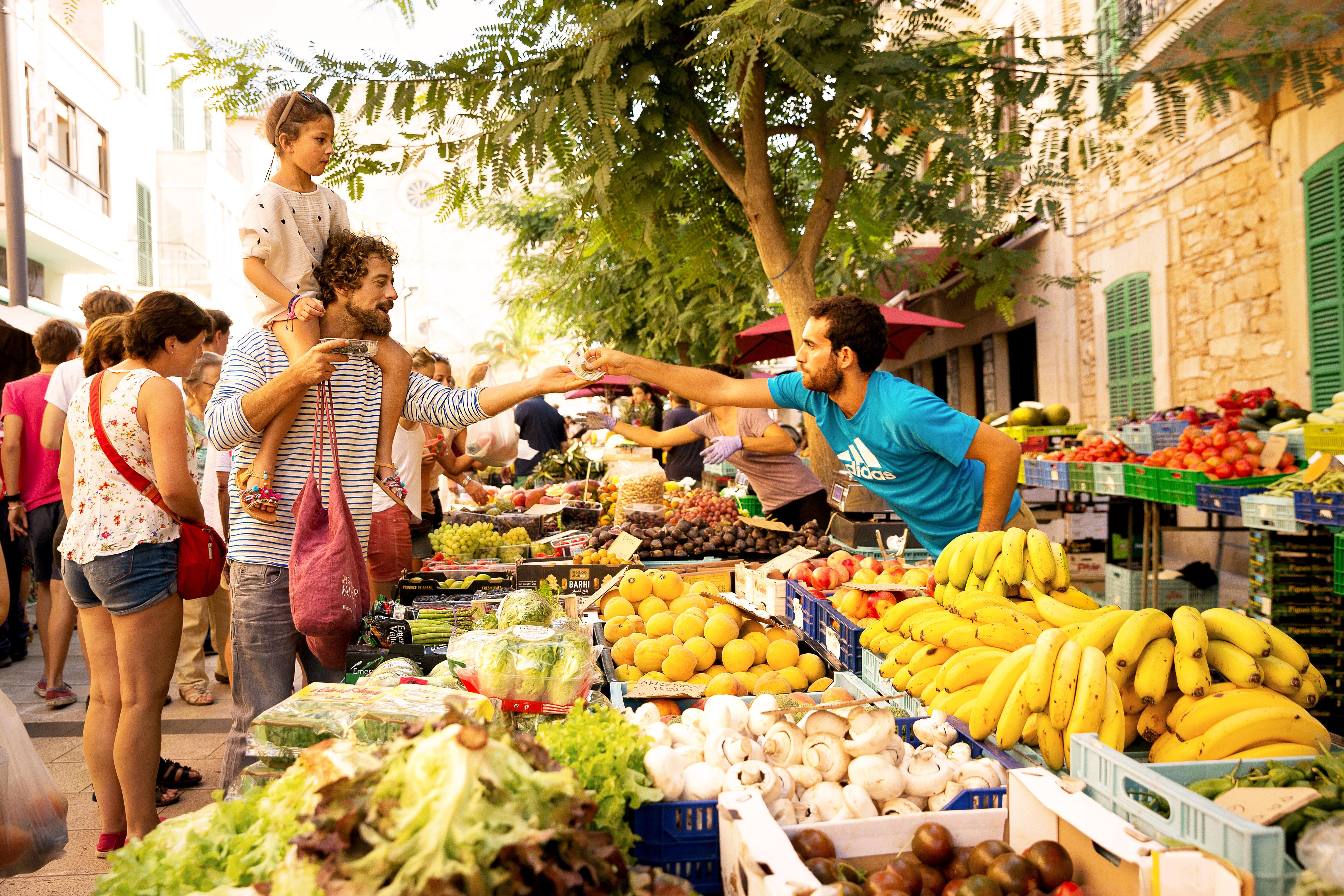 Far og datter handler frukt på et lokalt matmarked